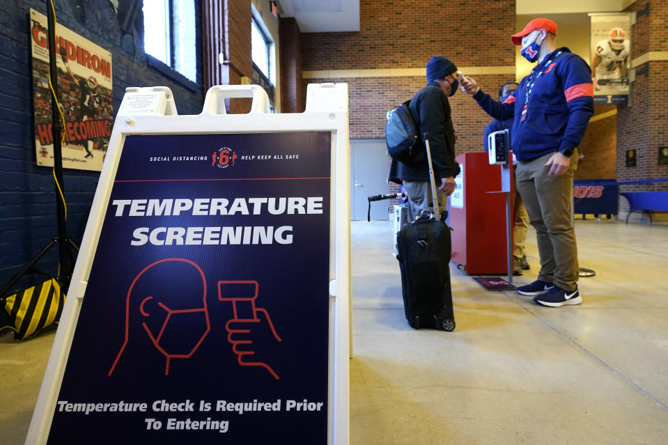 A photographer has his temperature checked as he arrives for an NCAA college football game between Illinois and Purdue Saturday, Oct. 31, 2020, in Champaign, Ill. (AP Photo/Charles Rex Arbogast)
