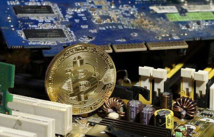FILE PHOTO: A copy of bitcoin standing on PC motherboard is seen in this illustration picture
