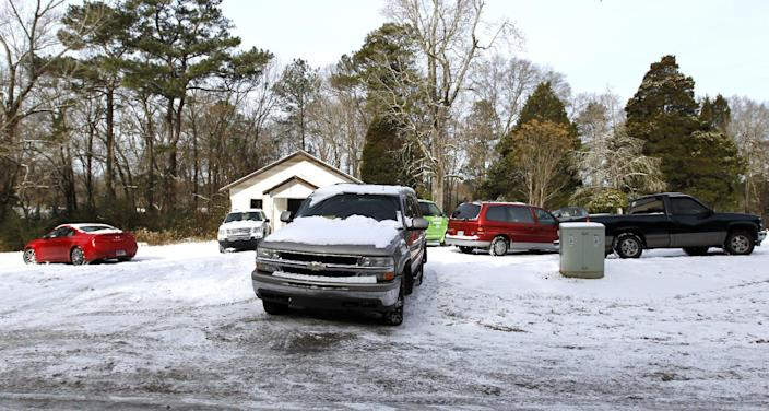 Cars are left in a vacant church parking lot as drivers abandoned their vehicles and walked home or found shelter nearby on Wednesday, Jan. 29, 2014, in Indian Springs, Ala. A winter storm caught much of Alabama off guard and thousands of people spent the night at work, school, and on roadways in their cars. (AP Photo/Butch Dill)