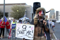 FILE - In this Nov. 5, 2020, file photo, Jacob Anthony Chansley, who also goes by the name Jake Angeli, a Qanon believer speaks to a crowd of President Donald Trump supporters outside of the Maricopa County Recorder's Office where votes in the general election are being counted, in Phoenix. Some followers of the QAnon conspiracy theory are now turning to online support groups and even therapy to help them move on, now that it's clear Trump's presidency is over. (AP Photo/Dario Lopez-Mills, File)