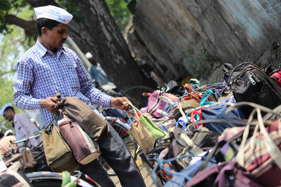 A lunchbox delivery man or Dabbawala gets ready to deliver the lunches to the workplace in Mumbai, India on 26 April 2019. (Photo by Himanshu Bhatt/NurPhoto via Getty Images)
