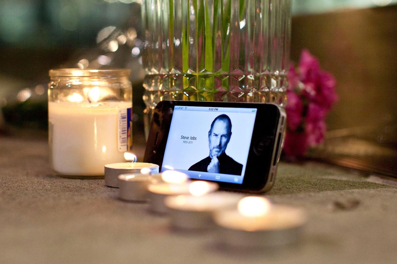 NEW YORK, NY - OCTOBER 05:  Candles, flowers, and an iPhone with Steve Jobs photo displayed, are seen in remembrance of Steve Jobs, founder and former CEO of Apple Inc, outside the Apple Store at West 66th Street on October 5, 2011 in New York City.Jobs, 56, passed away October 5, 2011 after a long battle with pancreatic cancer. Jobs co-founded Apple in 1976 and is credited, along with Steve Wozniak, with marketing the world's first personal computer in addition to the popular iPod, iPhone and iPad.  (Photo by Andrew Burton/Getty Images)