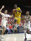 California guard Juhwan Harris-Dyson (2) drives between Arizona's Dusan Ristic (14) and Allonzo Trier during the first half of an NCAA college basketball game Saturday, March 3, 2018, in Tucson, Ariz. (AP Photo/Rick Scuteri)