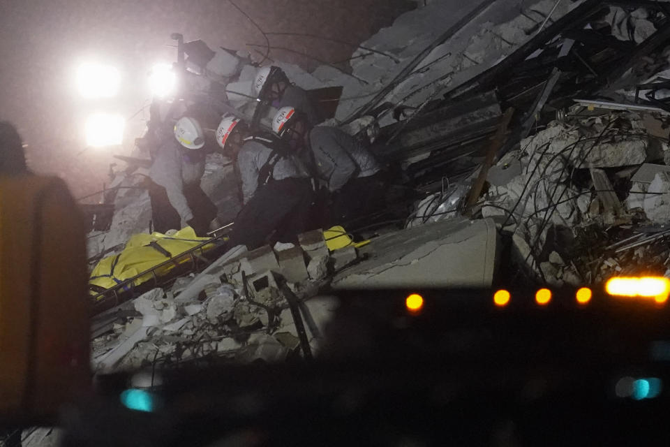 FILE - In this June 24, 2021, file photo, rescue workers remove a body from the rubble where a wing of a 12-story beachfront condo building collapsed in the Surfside area of Miami. Search and rescue teams from Miami-Dade have been described as among the best and most experienced in the world. (AP Photo/Gerald Herbert, File)