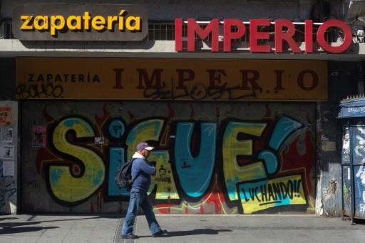 """A man walks past a boarded up shoe store in valparaiso with graffiti that reads """"Keep fighting!"""""""