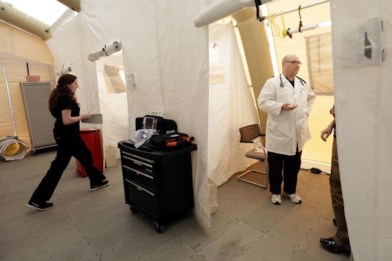 """Registered nurse Michelle Newbury, left, and physician assistant Scott Fillman meet with patients, not pictured, in a tent set up for a people with flu symptoms, just outside the emergency entrance at the Lehigh Valley Hospital Thursday, Jan. 10, 2013, in Allentown, Pa. The Pennsylvania Department of Health designated flu as now """"widespread"""" throughout the commonwealth. There have been more than 11,000 laboratory-confirmed flu cases in the state since the flu season began in mid-December. (AP Photo/Matt Rourke)"""