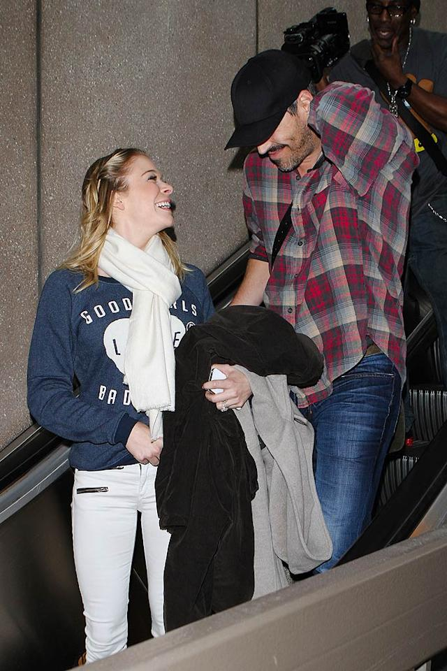 Newlyweds LeAnn Rimes and Eddie Cibrian looked happy to be back home in Los Angeles as they landed at LAX after a flight from Chicago on Sunday, despite the fact the paparazzi were on their tail. (11/21/2011)