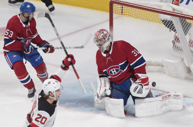 New Jersey Devils' Blake Coleman (20) celebrates a goal against Montreal Canadiens goaltender Carey Price by teammate Damon Severson (not shown) as Canadiens' Victor Mete (53) looks on during third-period NHL hockey game action in Montreal, Thursday, Nov. 28, 2019. (Graham Hughes/The Canadian Press via AP)
