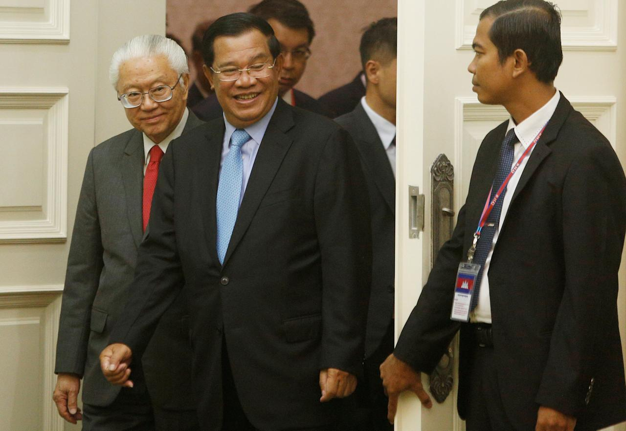 Singapore's president Tony Tan Keng Yam (L) and Cambodian Prime Minister Hun Sen (C) arrive for a signing ceremony between Cambodia and Singapore at the Prime Minister's office in Phnom Penh, Cambodia January 9, 2017. REUTERS/Samrang Pring