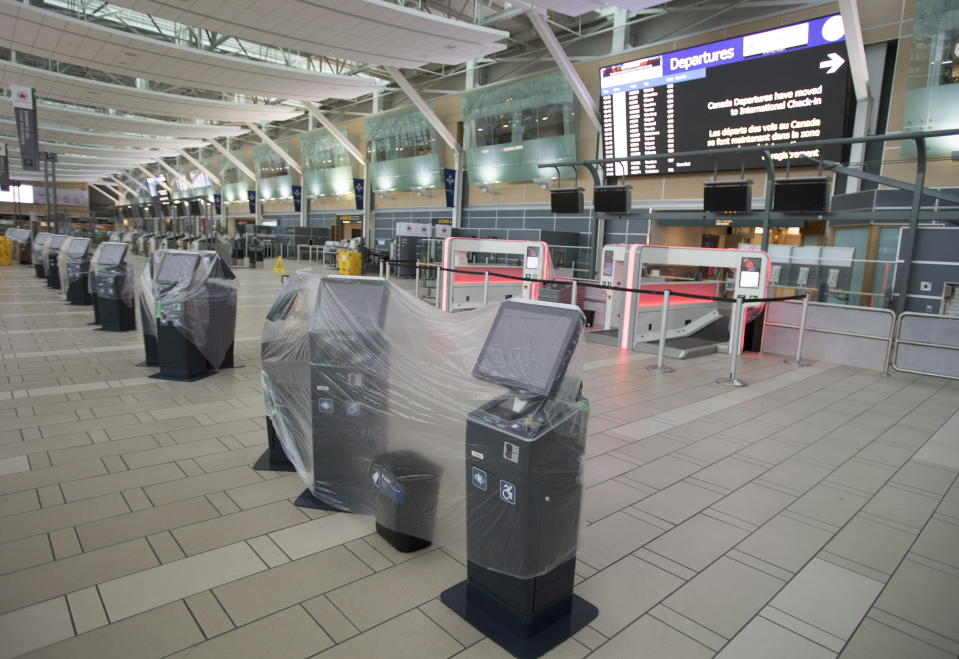 Check in Kiosks are covered in plastic at the domestic check in, at Vancouver International Airport, Tuesday, June 9, 2020. Airlines in Canada and around the world are suffering financially due to the lack of travel and travel bans due to COVID-19. (Jonathan Hayward/The Canadian Press via AP)