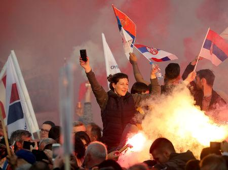 "Supporters of Serbian President Aleksandar Vucic burn flare as they wait for his arrival for his campaign rally ""The Future of Serbia"" in front of the Parliament Building in Belgrade, Serbia, April 19, 2019. REUTERS/Marko Djurica"