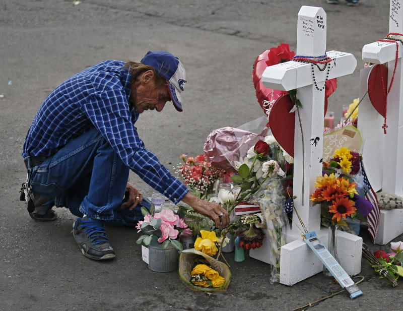 epa07759205 Antonio Basbo kneels in front of the cross for his partner Margie Reckard at the make shift memorial for the mass shooting that happened at a Walmart in El Paso, Texas, USA, 06 August 2019. Twenty two people killed and over forty injured from the mass shooting at the Walmart in El Paso, Texas on 03 August 2019. EPA/LARRY W. SMITH