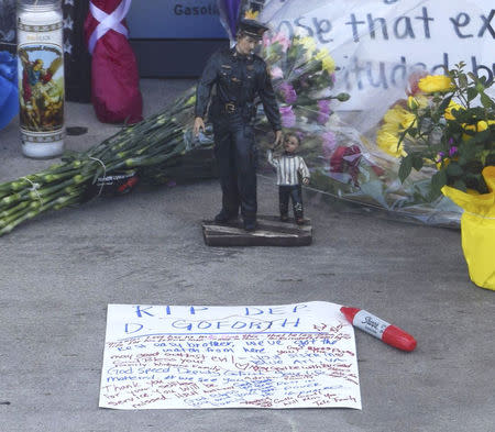 A statuette is seen near other mementos and messages left at the scene of a policeman's shooting in Houston