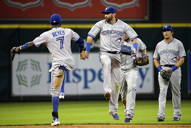 Toronto Blue Jays' Jose Reyes (7) and Jose Bautista, right, leap as the celebrate beating the Hosuton Astros in a baseball game Thursday, July 31, 2014, in Houston. The Blue Jays won 6-5. (AP Photo/David J. Phillip)