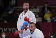 Steven de Costa of France, top, and Kalvis Kalnins of Latvia react during the men's kumite -67kg elimination round for Karate at the 2020 Summer Olympics, Thursday, Aug. 5, 2021, in Tokyo, Japan. (AP Photo/Vincent Thian)