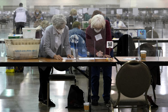 Election officials check ballots during a Milwaukee hand recount of Presidential votes at the Wisconsin Center, Friday, Nov. 20, 2020, in Milwaukee, Wis. The recount of the presidential election in Wisconsin's two most heavily Democratic counties began Friday with President Donald Trump's campaign seeking to discard tens of thousands of absentee ballots that it alleged should not have been counted. (AP Photo/Nam Y. Huh)