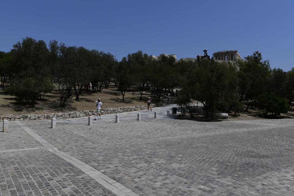 People walk under the ancient Acropolis, in Athens Greece, Tuesday, Aug. 3, 2021. Authorities in Greece have closed the Acropolis and other ancient sites during afternoon hours as a heatwave scorching the eastern Mediterranean continued to worsen. Temperatures reached 42 C (107.6 F) in parts of the Greek capital, as the extreme weather fueled deadly wildfires in Turkey and blazes across the region. (AP Photo/Michael Varaklas)