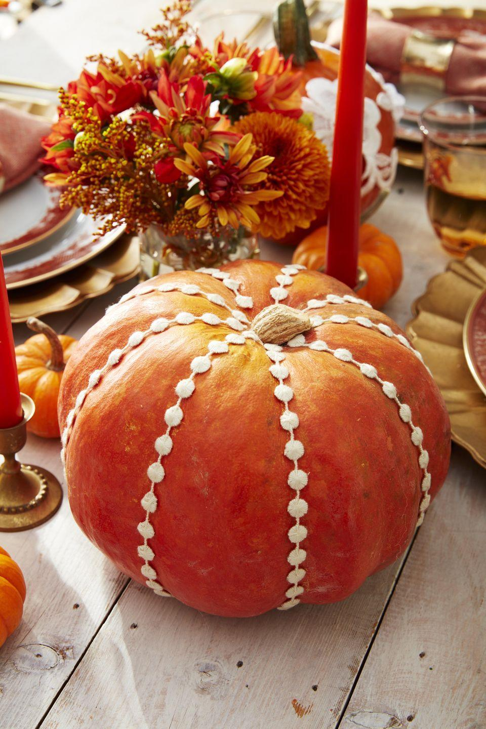 <p>Not just for wedding dresses! Hot glue lace and sewing trim on orange pumpkins and sprinkle them down the center of the table. An orange flower and bittersweet floral arrangement round out the scene.<br></p>