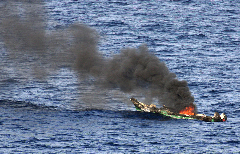 FILE - In this Saturday, April 10, 2010 file photo released by the U.S. Navy, a suspected pirates' skiff burns after being destroyed near the amphibious dock landing ship USS Ashland, part of the Nassau Amphibious Ready Group and 24th Marine Expeditionary Unit, at sea in the Gulf of Aden, about 330 nautical miles off the coast of Djibouti. World sea piracy fell for a third straight year in 2013, as Somali pirates were curbed by international naval patrols and improved ship vigilance, an international maritime watchdog said Wednesday, Jan. 15, 2014. (AP Photo/U.S. Navy, Chief Fire Controlman Harry J. Storms, File)
