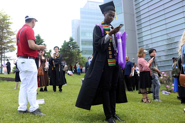 Richard Nicholls, 22, a graduate in engineering from The City College of New York is on his phone after his commencement ceremony in Manhattan on May 31, 2019. When asked about the issues he is most concerned about leading up to the 2020 election, he said,
