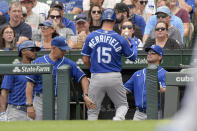 Kansas City Royals' Whit Merrifield (15) enters the dugout after scoring on wild pitch against the Chicago Cubs during the first inning of a baseball game Saturday, Aug. 21, 2021, in Chicago. (AP Photo/Mark Black)