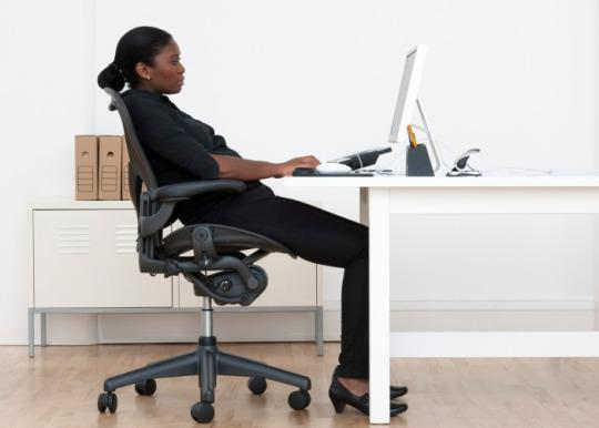 Female employee sitting at desk looking at a computer screen