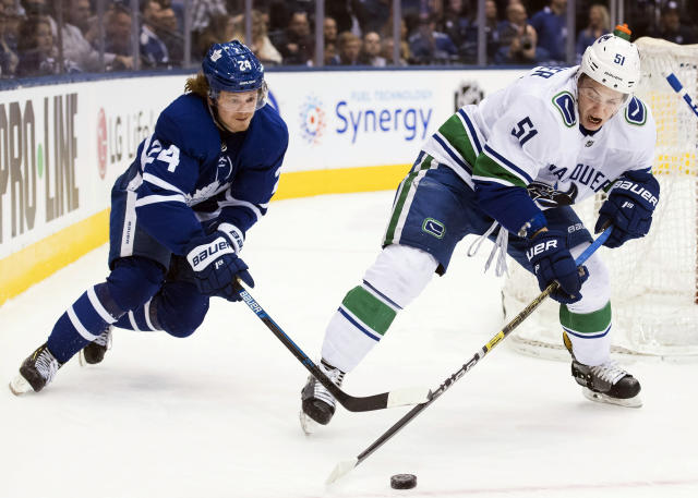 Toronto Maple Leafs right wing Kasperi Kapanen (24) steals the puck from Vancouver Canucks defenseman Troy Stecher (51) during the third period of an NHL hockey game, Saturday, Jan. 5, 2019, in Toronto. (Nathan Denette/The Canadian Press via AP)