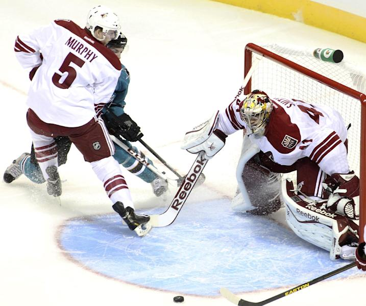 Phoenix Coyotes goalie Mike Smith tracks the puck in front of the crease as Connor Murphy (5) checks a San Jose Shark during the first period of an NHL preseason hockey game in San Jose, Calif., Saturday, Sept. 21, 2013. (AP Photo/Mathew Sumner)