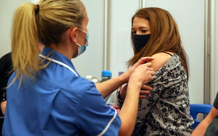 Caroline Nicolls receive an injection of the Moderna Covid-19 vaccine administered by nurse Amy Nash