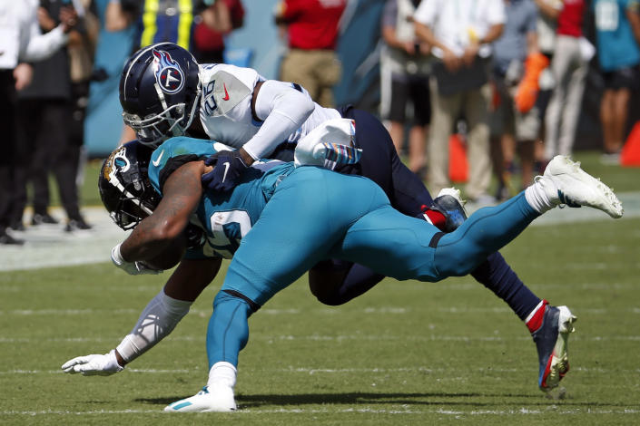 Jacksonville Jaguars running back James Robinson, left front, is stopped by Tennessee Titans cornerback Kristian Fulton after a short gain during the first half of an NFL football game, Sunday, Oct. 10, 2021, in Jacksonville, Fla. (AP Photo/Stephen B. Morton)