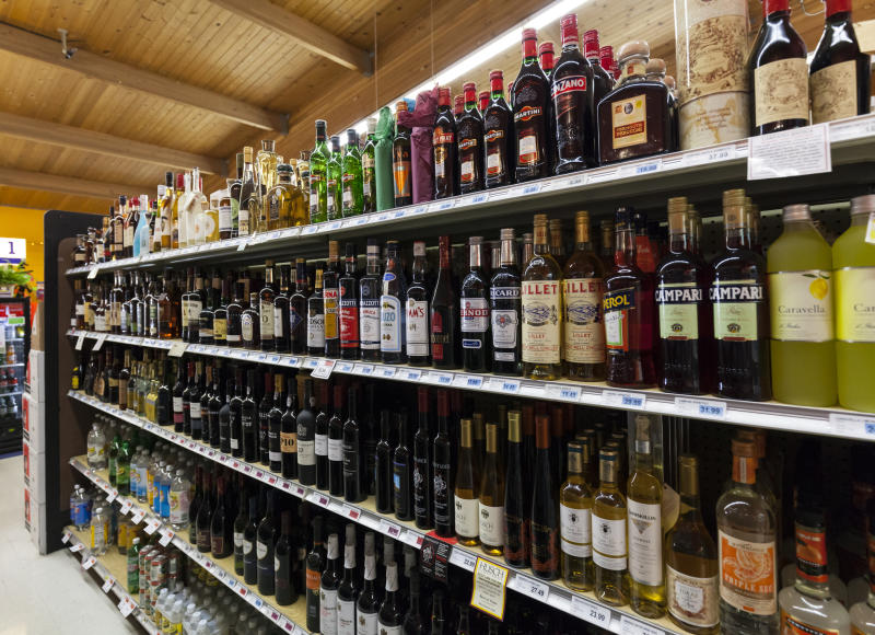 An aisle in a bottle shop showing alcohol spirits on a shelf.
