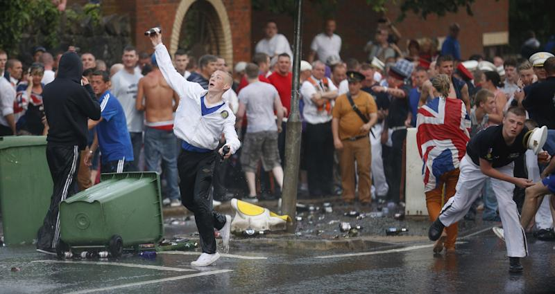 Loyalists attack riot police close to the Ardoyne area of North Belfast, Northern Ireland, Friday, July 12, 2013. Protestant hardliners attacked lines of Belfast riot police Friday as Northern Ireland's annual mass marches by the Orange Order brotherhood reached a furious, chaotic end with running street battles at several urban conflict zones. (AP Photo/Peter Morrison)