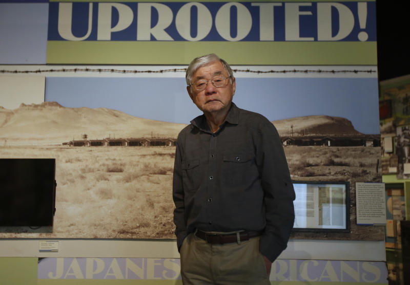 """In this photo taken Tuesday, Feb. 11, 2020, Les Ouchida poses at the permanent exhibit titled """"UpRooted Japanese Americans in World War II"""" at the California Museum in Sacramento, Calif. Ochida, who is a docent for the exhibit, was a child when his family was forced to move in 1942 from their home near Sacramento to an internment camp in Arkansas. Assemblyman Al Muratsuchi, D-Torrence has introduced a resolution to apologize for the state's role in carrying out the federal government's internment of Japanese-Americans. A similar resolution will be brought up before the state Senate by Sen. Richard Pan, D-Sacramento. (AP Photo/Rich Pedroncelli)"""
