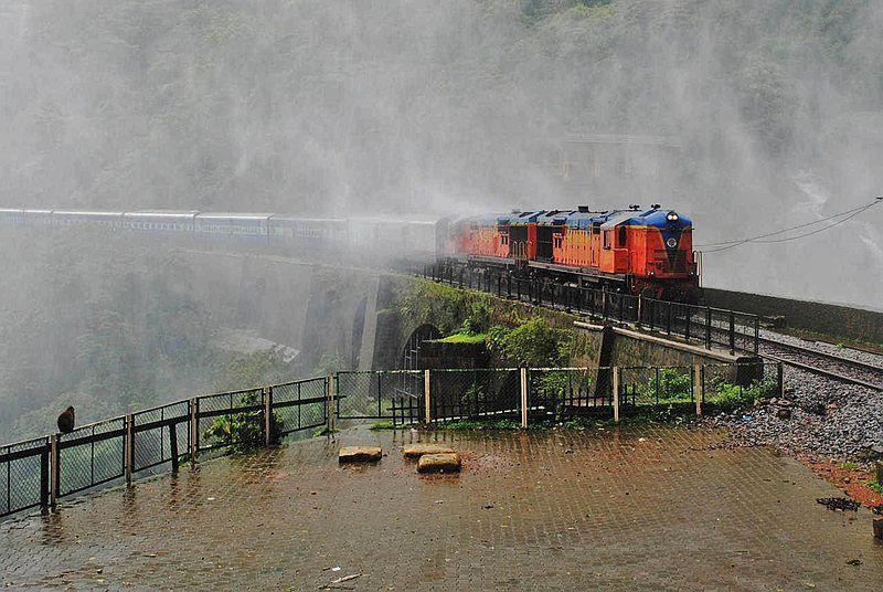 Through veils of misty rain, a rake hauled by twin locomotives equipped with Auto Emergency Brakes carefully negotiates the viaduct across the Dudhsagar Falls.