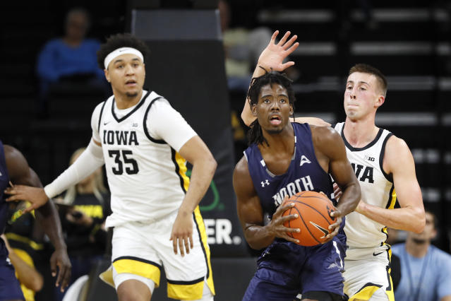 North Florida forward Wajid Aminu, center, passes between Iowa's Cordell Pemsl, left, and Joe Wieskamp, right, during the first half of an NCAA college basketball game, Thursday, Nov. 21, 2019, in Iowa City, Iowa. (AP Photo/Charlie Neibergall)