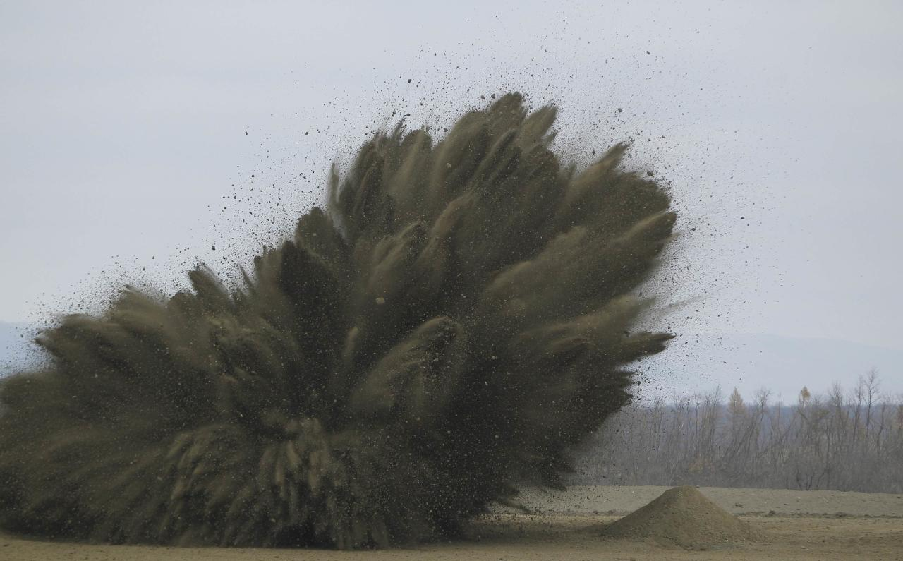 Munitions (L) are destroyed in a controlled blast at the U.S. Army Letterkenny Munitions Center in Chambersburg, Pennsylvania November 19, 2012. The mound on right shows the pre-explosion dirt mound used. Staff at Letterkenny Army Depot detonated the three-decade-old explosives because they said that the munitions were at risk of becoming dangerously unstable in storage. Photo taken November 19, 2012. To match Special Report USA-PENTAGON/WASTE REUTERS/Gary Cameron (UNITED STATES - Tags: MILITARY BUSINESS POLITICS)