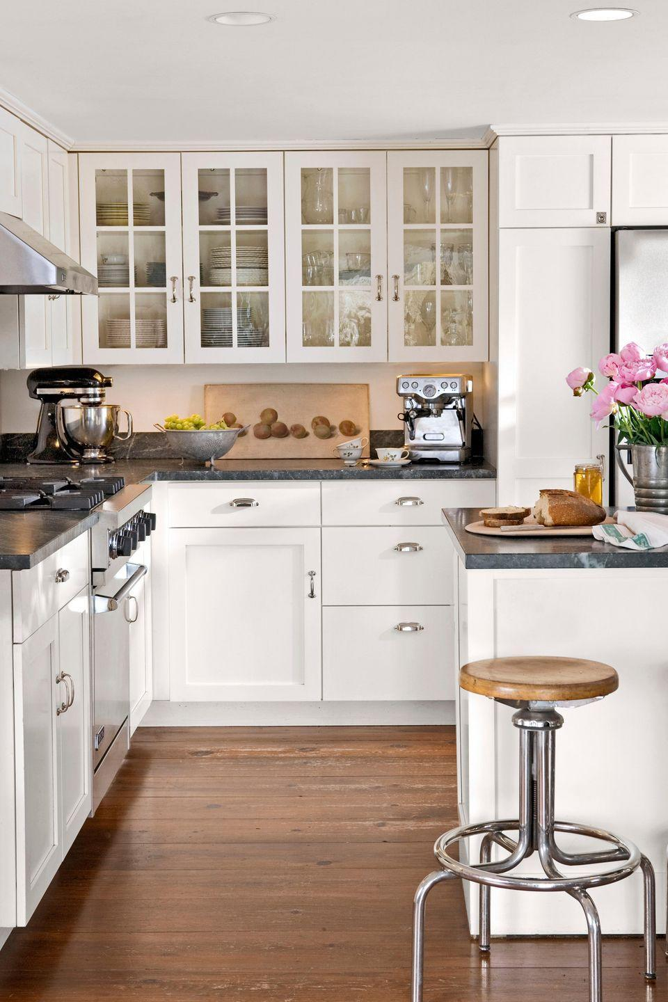 <p>Soapstone counters, vintage lab stools, and a bank of whitewashed wooden cabinets add to the warmth of an already sunny, small white kitchen.</p>