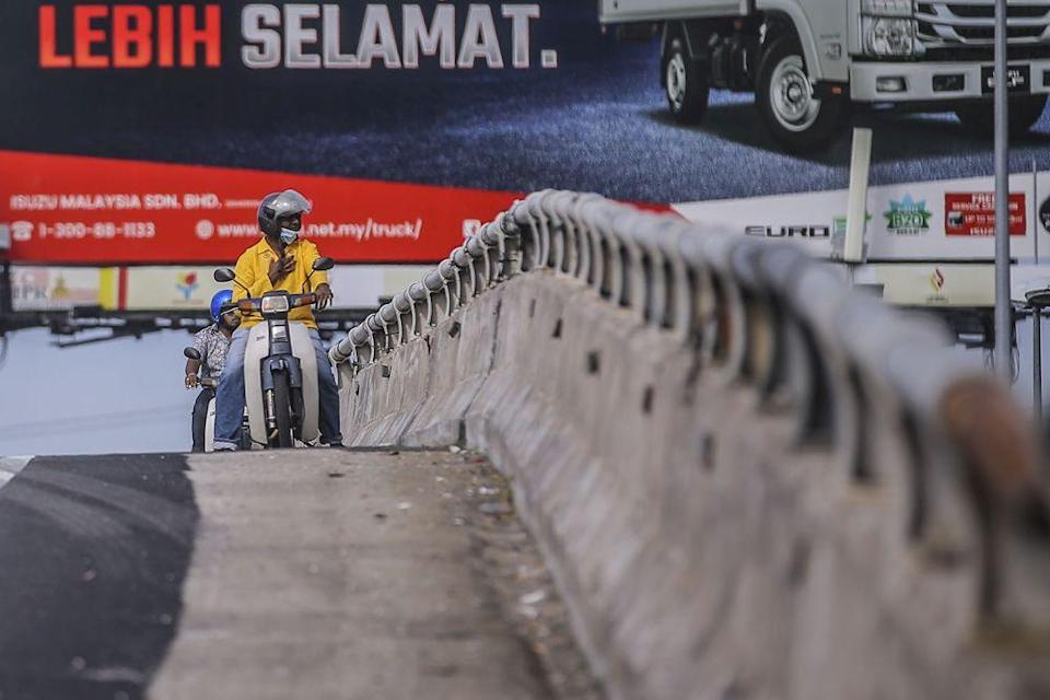 Motorcyclists stop for a quick prayer by the side of a flyover overlooking Batu Caves during Thaipusam January 28, 2021. — Picture by Hari Anggara
