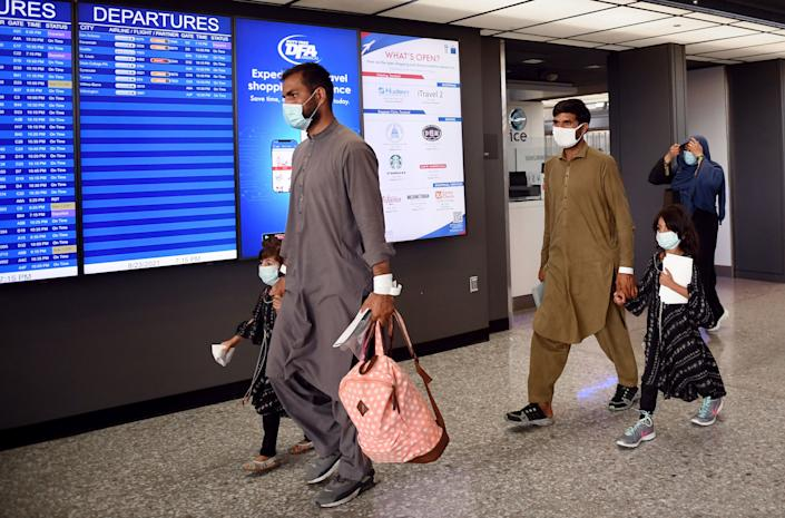 Afghan refugees walk to board a bus after arriving on a flight at Dulles International Airport in Chantilly, Virginia on August 23, 2021. (Olivier Douliery/AFP via Getty Images)