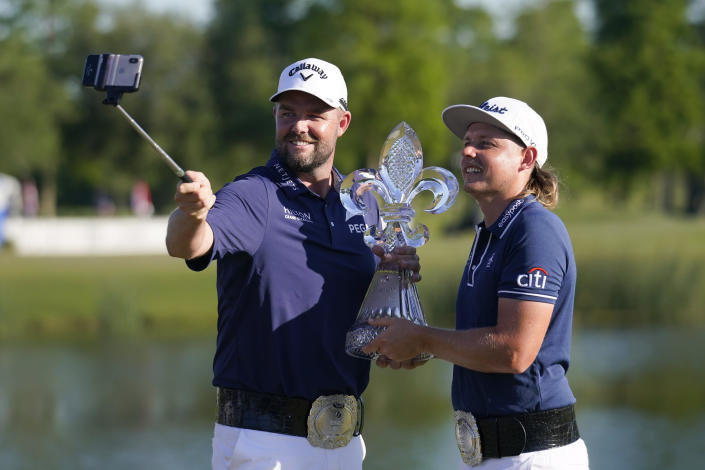 Marc Leishman, of Australia, left, and teammate Cameron Smith, of Australia, hold the trophy after winning the PGA Zurich Classic golf tournament at TPC Louisiana in Avondale, La., Sunday, April 25, 2021. (AP Photo/Gerald Herbert)