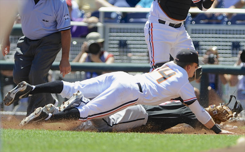 Louisville's Cole Sturgeon, bottom, is tagged out by Oregon State second basemen Andy Peterson (14) during a run down between first and second bases in the first inning of an NCAA College World Series baseball game in Omaha, Neb., Monday, June 17, 2013. (AP Photo/Eric Francis)