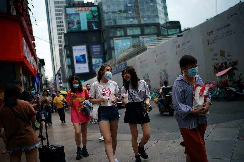 People wearing face masks walk at a shopping area in Chengdu