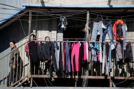 FILE PHOTO: People stand outside a low-cost dwelling at a village in Tongzhou district of Beijing