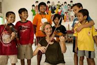 This picture taken on November 29, 2013, shows Italian violinist Sara Michieletto playing violin for street children at a shelter for less fortunate children in Bekasi, on the outskirts of Jakarta