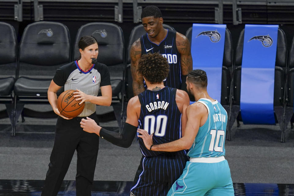 Referee Natalie Sago, left, puts the ball in play during the second half of an NBA basketball game between the Orlando Magic and the Charlotte Hornets, Monday, Jan. 25, 2021, in Orlando, Fla. Natalie Sago and Jenna Schroeder made up two-thirds of the crew assigned to the Charlotte at Orlando game, the first time in NBA history that two women were assigned to work a regular-season contest together. (AP Photo/John Raoux)