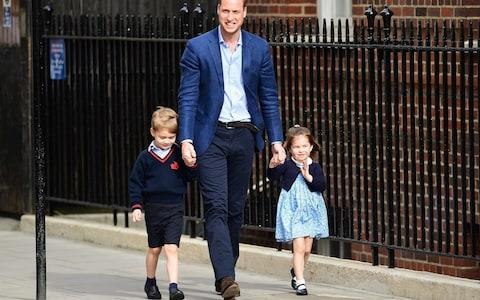The Duke of Cambridge grins at the cameras, flanked by his eldest son Prince George and a waving Princess Charlotte - Credit: DASA