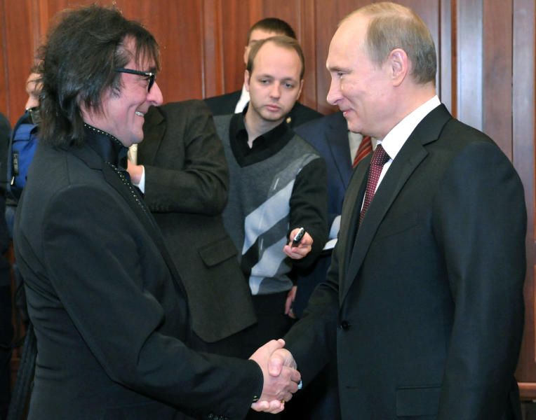 "FILE- In this Jan. 24, 2013, file photo, Russian President Vladimir Putin, right, shakes hands with famous Russian musician Yuri Bashmet on his 60th birthday, at the Kremlin in Moscow. When famed viola player Yuri Bashmet declared that he ""adored"" President Vladimir Putin, he stirred little controversy in a country where classical musicians have often curried favor with the political elite. But political drama spilled into the orchestra pit last month when Bashmet refused to condemn a new law prohibiting Americans from adopting Russian children, and in response the beloved singer Sergei Nikitin canceled his appearance at a concert celebrating the violist's 60th birthday. (AP Photo/RIA Novosti, Alexei Nikolsky, Presidential Press Service, File)"