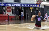A man wades across a street as people buy products at a store in La Lima near San Pedro Sula in Honduras