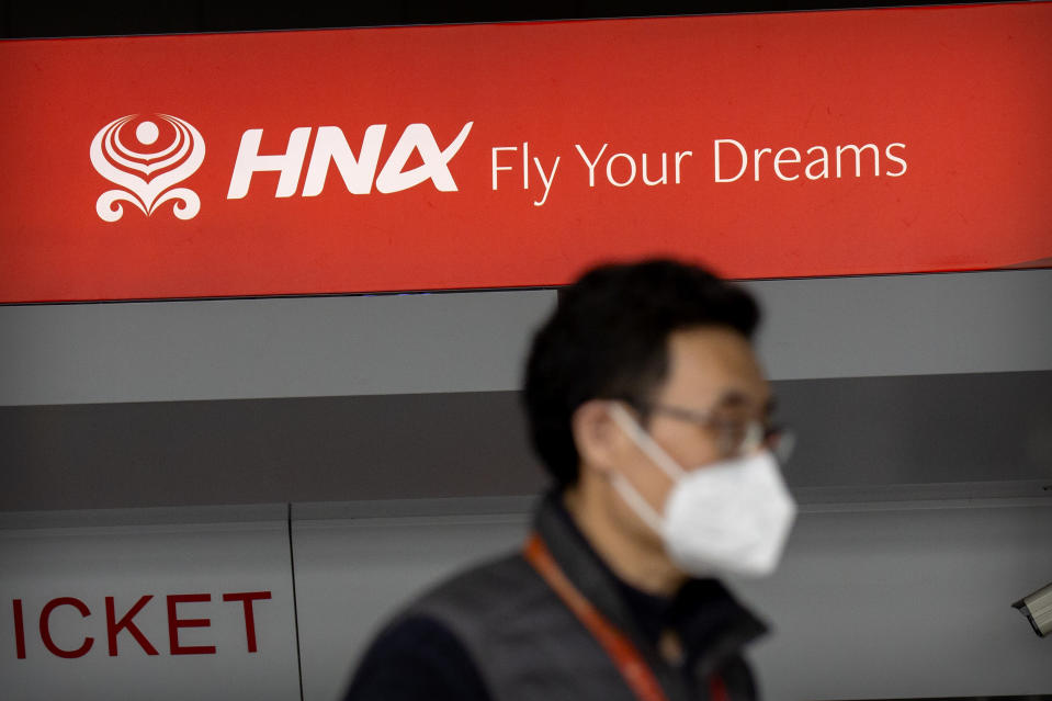 A man wearing a face mask to protect against the spread of the coronavirus walks past a ticket counter for Hainan Airlines, owned by Chinese firm HNA Group, at Beijing Capital International Airport in Beijing, Friday, March 6, 2020. HNA Group, a debt-burdened Chinese airline operator that faced opposition in Washington to its attempt to buy a Wall Street hedge fund during a costly global acquisition spree, says its creditors have asked a court to declare the company bankrupt. (AP Photo/Mark Schiefelbein)