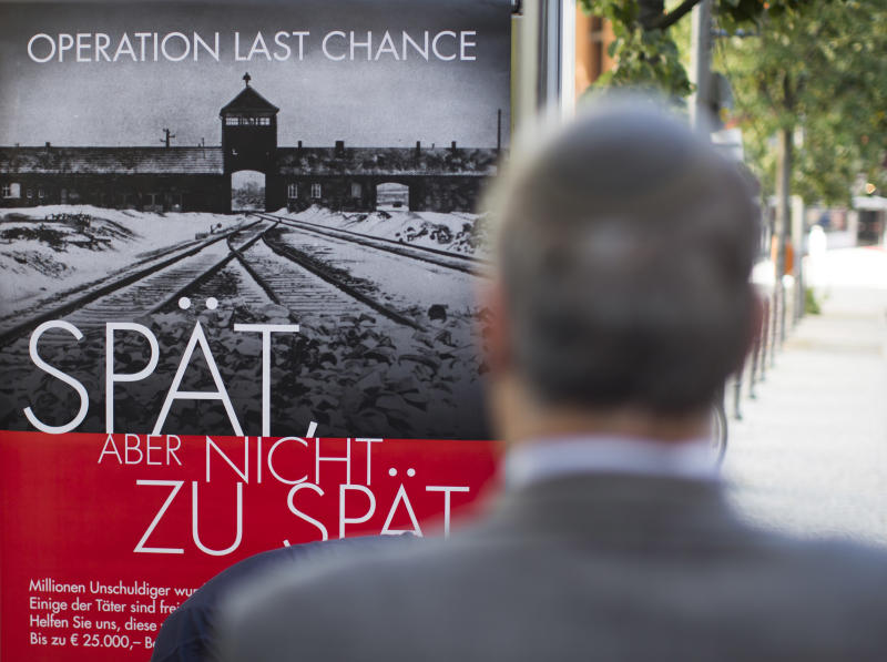 """Efraim Zuroff, the top Nazi-hunter of Simon Wiesenthal Center, stands in front of a placard reading """"Operation last chance - late but not too late"""" displayed in Berlin, Germany, Tuesday, July 23, 2013. With 2,000 placards in Berlin, Hamburg and Cologne cities the Simon Wiesenthal Center launched another campaign to find and prosecute Nazi war criminals while they are still alive. Efraim Zuroff, the center's top Nazi-hunter, told reporters in Berlin that """"Operation Last Chance II"""" would provide up to euro 25,000 (US$ 32,800) in reward money for information that leads to the investigation and prosecution of war criminals. (AP Photo/Gero Breloer)"""